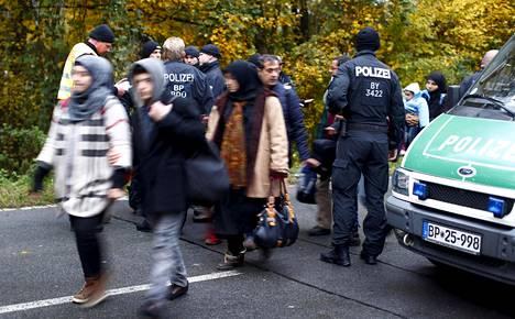 Poliisi tutki Itävallasta saapuneiden maahanmuuttajien papereita Passaun raja-asemalla Saksassa lokakuussa 2015.
