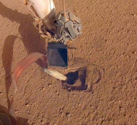 Insightin lämpömittari ei ole päässyt syvälle Marsin pinnan alle. Nyt avuksi on tuotu robottikäsi, josta osa näkyy osa kuvan yläosassa.