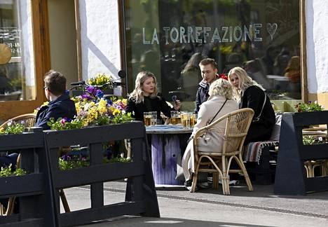 Vapunviettäjiä Helsingin keskustassa ravintolan terassilla vappuaattona 2021.
