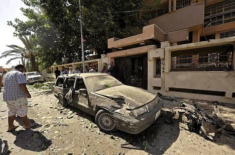Mies tutki räjähdyspaikkaa Ruotsin konsulaatin ulkopuolella Bengasissa perjantaina.