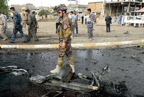Sotilas tutki autopommin räjähdyspaikkaa lähellä Kirkukia torstaina.