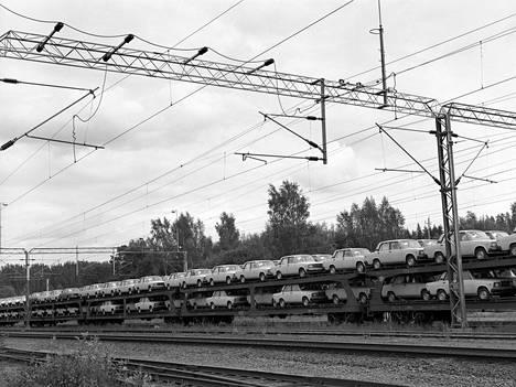 """Lada-henkilöautoja tuodaan rautateitä pitkin Neuvostoliitosta Suomeen (Lappeenranta, Simola, 1986-1987). """"Neuvostoliiton historian loppuaikoina 1980-luvulla Lada oli yksi Suomen yleisimmistä automerkeistä. Seuraavalla vuosikymmenellä käytetyt Ladat myytiin Suomesta takaisin Venäjälle."""""""