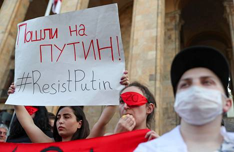 Mielenosoittajat kokoontuivat Tblisin parlamenttitalon edustalle perjantai-iltana.