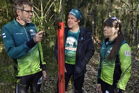 Jussi Suonio (vas.), Jussi Näri ja Kaija Järvi näyttävät metsässä Hämeenlinnassa tolpan, joka osoitti aikanaan supervaltojen välisen kuuman linjan sijainnin maan alla.