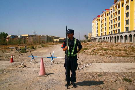 Kiinalainen poliisi seisoi tiellä, joka johtaa uiguurien keskitysleirille Yiningissä Xinjiangissa syyskuussa 2018.