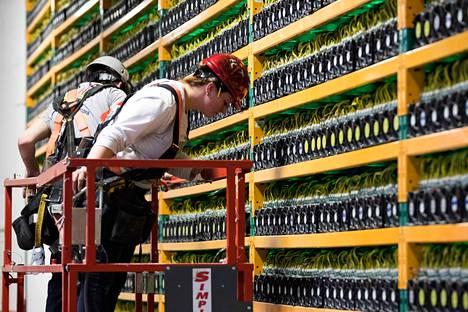 Työntekijät tarkastivat laitteita bitcoinin louhintaan tarkoitetussa tietokonekeskuksessa Kanadan Quebecissä viime maaliskuussa. Louhimiseksi sanotaan tietokoneella tehtyä laskentaa, jolla varmennetaan kryptovaluutan kirjanpitotietokantaa ja luodaan uusia bitcoineja.