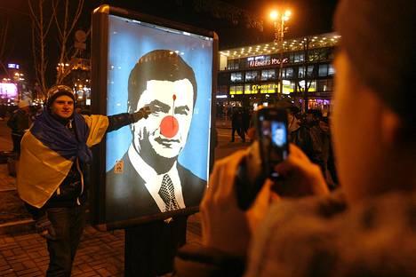 Mielenosoittaja seisoo presidentti Viktor Janukovytšin töhrityn kuvan vieressä Kiovassa. Tiistaina tuhannet ihmiset vaativat presidentin eroa Ukrainassa.