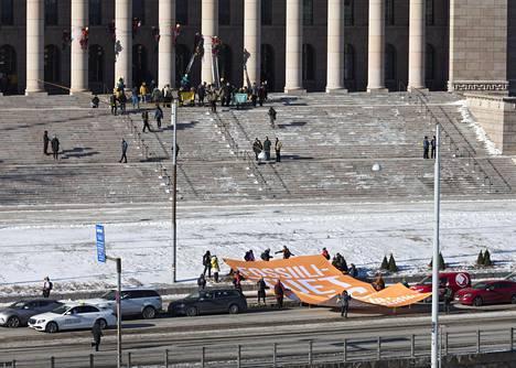 Mielenosoittajat kiipesivät eduskuntatalon pylväisiin ja kuljettivat Mannerheimintien yli ison banderollin keskiviikkona aamupäivällä.