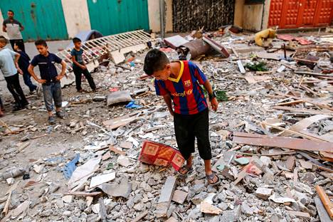 Palestiinalaiset lapset tutkivat Israelin ilmaiskussa tuhoutuneen rakennuksen raunioita tiistaina Gazassa.