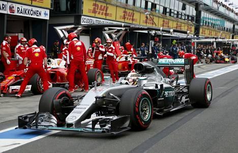 Lewis Hamilton hallitsi kauden ensimmäisen F1-kisan aika-ajon mielensä mukaan. Taustalla Ferrari-tallin miehistöä.