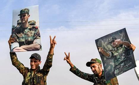 Syyrialaissotilaat nostivat johtajansa Bashar al-Assadin kuvia ilmaan tiistaina Manbijin kaupungissa Pohjois-Syyriassa.