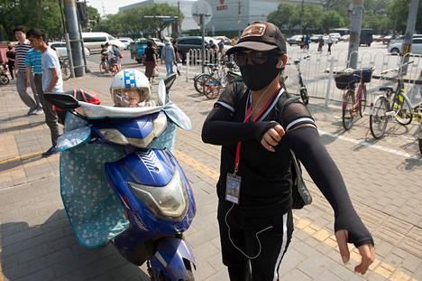 """Wu Jinghua, 41, suojautuu auringolta ajaessaan skootterilla. """"Kuumuus ei ole ongelma, mutta ruskettuminen on."""""""