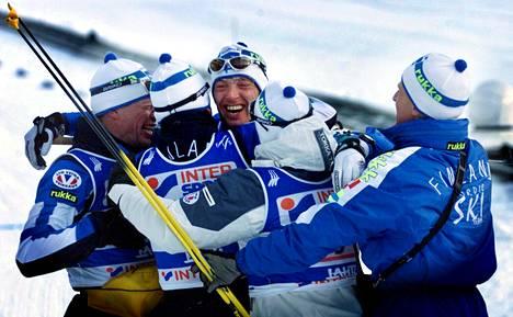 Suomen ankkuriosuuden hiihtänyt Mika Myllylä (kesk.) sai onnitteluja Harri Kirvesniemeltä, Sami Revolta, Janne Immoselta ja valmentaja Kari-Pekka Kyröltä, kun Suomen miesten joukkue oli ottanut kultamitalin viestissä Lahden MM-kisoissa 2001. Repo oli joukkueesta ainoa, joka ei kärynnyt dopingista.