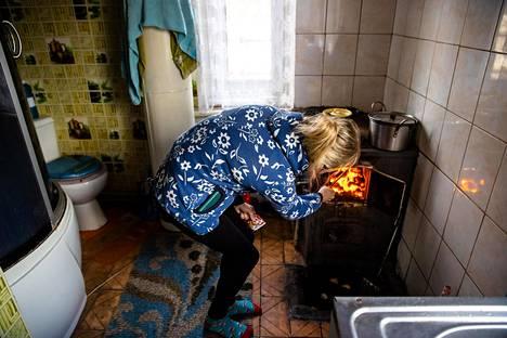 Inna Anatoljevna panee lisää hiiltä kamiinaan keittiössä, joka on myös wc ja suihkuhuone.