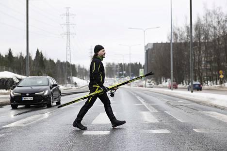 Poppis Suomela ylitti katua sukset ja sauvat käsissään Pitäjänmäen maisemissa Helsingissä.
