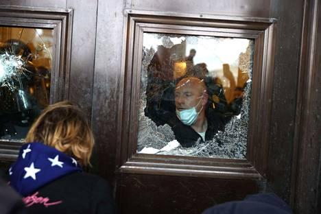 Kongressitalon poliisi katsoi ulos mielenosoittajien rikkomasta ikkunasta.
