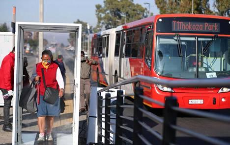 Linja-automatkustaja käveli desinfiointiainepilven läpi Sowetossa, Etelä-Afrikassa 14. päivä toukokuuta.