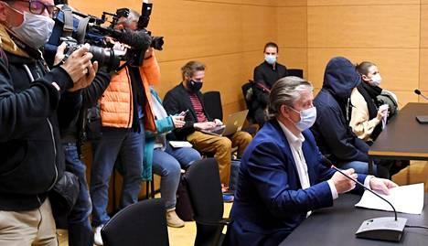 Kolmen murhasta epäillyn pojan vangitsemisoikeudenkäynti alkoi Helsingin käräjäoikeudessa torstaina. Edessä asianajaja Seppo Heikkilä, taustalla oikeudenkäyntiä seuraavia henkilöitä.