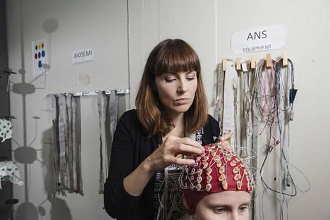 Aivotutkija Katri Saarikiven mukaan podcastien vaikutusta aivotoimintaan ei ole juuri tutkittu. Helsingin yliopiston kognitiivisen aivotutkimuksen yksikön laboratoriossa aivojen toimintaa mitataan esimerkiksi aivosähkökäyrää kuvantavien EEG-myssyjen sekä kehoon kiinnitettävien elektrodipiuhojen avulla. Kuva on otettu 2017.