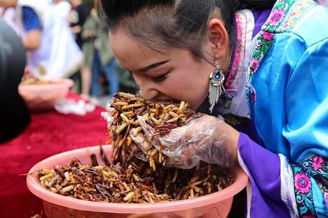 Naiskilpailija yrittää tehdä selvää annoksestaan hyönteisten syöntikilpailussa sunnuntaina Lijiangissa, kiinalaisessa Yunnanin maakunnassa.