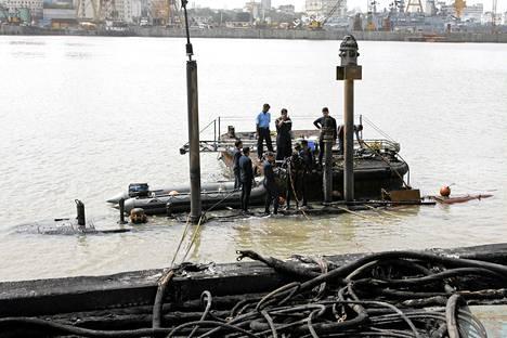 Intian puolustusministeriön kuvassa armeijan sukeltajat valmistautuvat tuhoutuneen sukellusveneen komentotornin katolla.