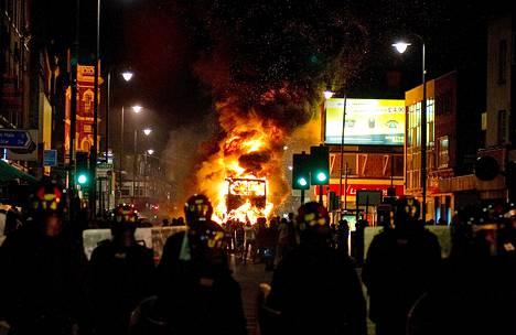 Kaksikerroksinen bussi palaa poliisirivistön takana Lontoon mellakoissa elokuussa.