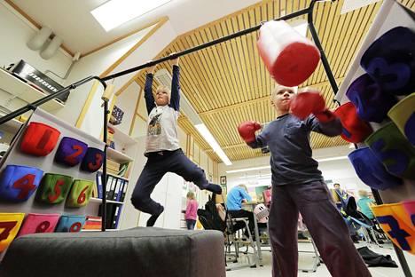 Viljami Halttu roikkuu ja Vili Grekula nyrkkeilee luokkahuoneen temppuradalla Kiimingin Alakylän koululla.