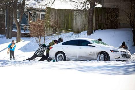 Ihmiset työnsivät lumeen juuttunutta autoa Austinissa, Texasissa 15. helmikuuta.