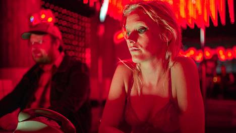 Nainen (Laura Birn) herää muovikääreestä rannalla ja lähtee kumoamaan miesten valtaa. Taustalla sivullinen tarkkailijamies (Lauri Maijala).