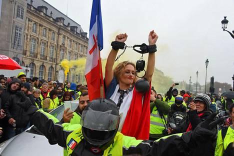 Kahleisiin ja Ranskan lippuun sonnustautunut nainen osallistui viime lauantaina keltaliivien mielenosoitukseen Ranskan Bordeaux'ssa. Nyt osa keltaliiveistä on aktivoitunut myös ilmastoasioissa.