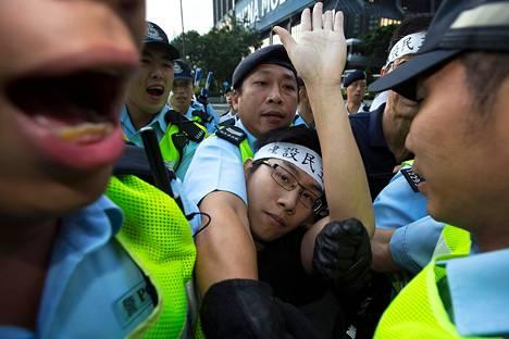 """Poliisit pidättelivät demokratia-aktivistia Kiinan kansallispäivän mielenosoituksessa 1. lokakuuta 2013. Aktivistin pääpannassa lukee: """"Rakentakaa demokraattinen Kiina""""."""