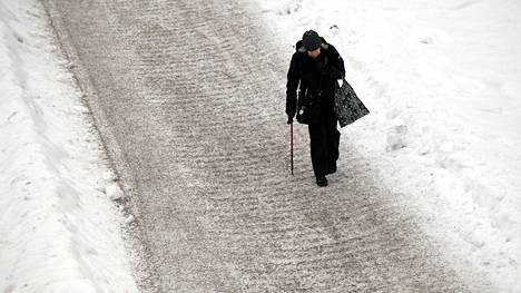 Jalankulkijoita on varoitettu jäätävän sateen aiheuttamasta erittäin liukkaasta säästä eteläisessä Suomessa. Jalankulkija huolella hiekoitetulla jalkakäytävällä Espoossa maanantaina.