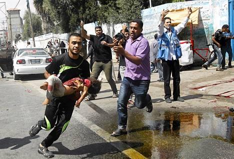 Mies kantaa loukkaantunutta lasta Israelin armeijan iskettyä YK:n kouluun sunnuntaina.