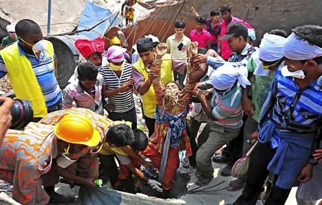 Pelastustyöntekijät vetivät eloonjäänyttä sortuneen tekstiilitehtaan raunioista Savarissa Bangladeshissa torstaina.