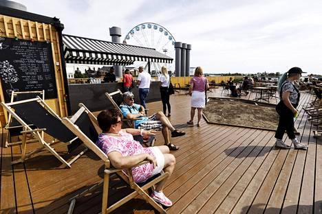Viikonlopun sääennuste näyttää siltä, että terassilla pärjää suuressa osassa Suomea ilman sateenvarjoa. Kuvassa lomailijoita Allas-merikylpylässä Helsingissä kesäkuussa.