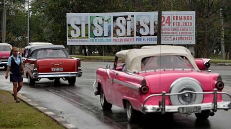 Turistien suosimat vanhat amerikkalaiset autot ajavat perustuslakia mainostavien Sí- eli Kyllä-kylttien edestä Havannassa 13. helmikuuta.