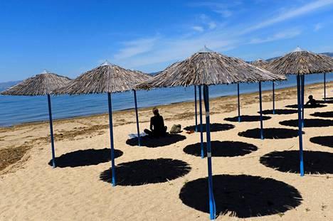 Yksinäinen rantalomailija istui aurinkovarjon suojassa Peraian rannalla Kreikan Thessalonikissa 5. toukokuuta.