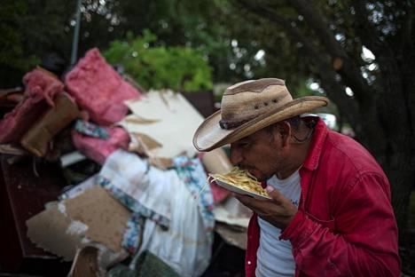 Tulvatuhoja raivannut Ruben Morales joutuu syömään pasta-annostaan ilman ruokailuvälineitä Houstonissa maanantaina.