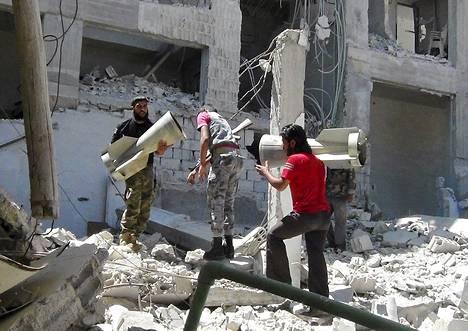 Kapinallistaistelijat kantoivat ammusten osia Douritin kylässä Latakiassa vielä lauantaina.