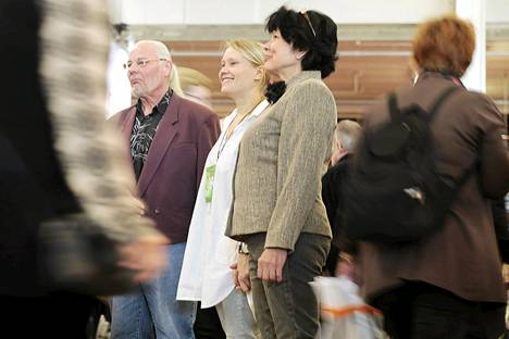 Elina Latva pitää kädestä Pekka Virtasta ja Arja Erikssonia kirjamessuilla.