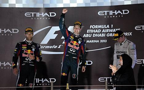 Sebastian Vettel juhli Abu Dhabin GP:n voittoa vierellään Nico Rosberg (oik) ja Mark Webber.