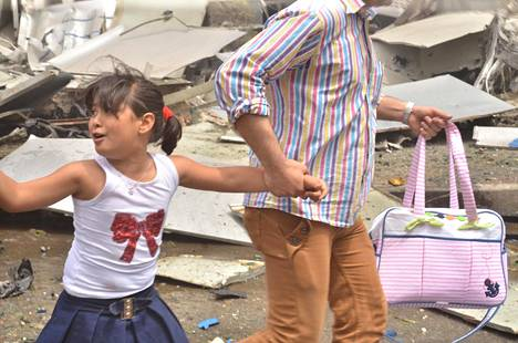 Siviilit pakenivat kapinallisten pommituksia Syyrian hallituksen hallitsemalla alueella Aleppossa keskiviikkona. Kuvan on luovuttanut Syyrian valtio-omisteinen uutistoimisto Sana.