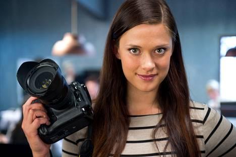 Taideopiskelija Raita Halikko (Krista Kosonen) työskentelee valokuvaajana juorulehden toimituksessa.