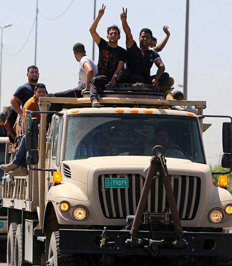 Irakin armeijan avuksi tulleet vapaaehtoiset näyttivät voitonmerkkiä, kun he lähtivät värväyskeskuksesta Bagdadissa sunnuntaina.