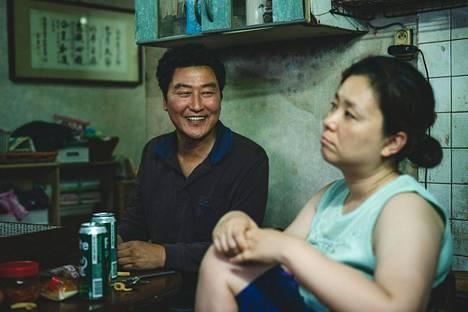 Kimit asuvat maanpinnan alapuolella kellarissa. Song Kang-ho näyttelee työtöntä isää ja perheen äitiä, entistä moukarinheittäjää näyttelee Chang Hyae-jin.
