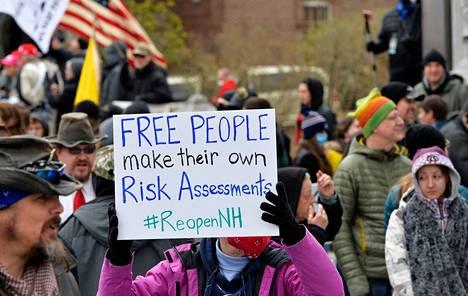 """Yhdysvalloissa osoitettiin mieltä poikkeustoimia vastaan viime viikonloppuna. """"Vapaat ihmiset tekevät omat riskiarvionsa"""", totesi mielenosoittajan kyltti Concordin kaupungissa New Hampshiressa."""