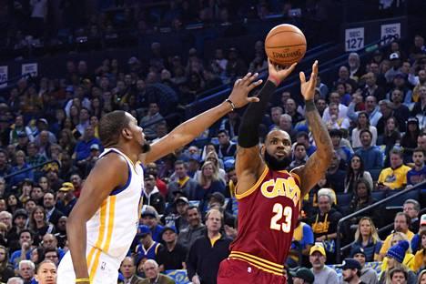 Golden Staten Kevin Durant yritti estää Clevelandin LeBron Jamesin (23) heiton tammikuun 16. päivä pelatussa ottelussa. James tavoittelee jo neljättä mestaruuttaan,