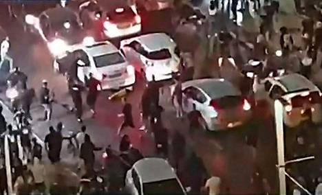 Kuvakaappaus israelilaisen tv-kanavan suorasta lähetyksestä, jossa näkyi, kuinka äärioikeistolaiset juutalaiset hyökkäsivät arabiksi olettamansa miehen kimppuun Bat Yamissa.