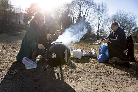 Muusikkokaverukset Anna Husgafvel (vas), Kalle Kurikkala ja Tommi Asplund grillasivat makkaraa Paavalin kirkon puistossa Vallilassa.