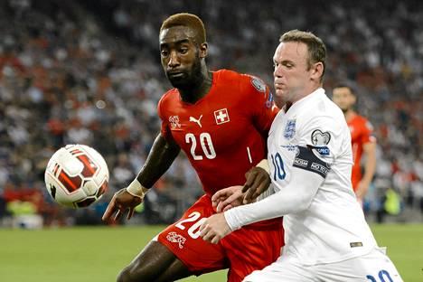 Englannin Wayne Rooney ja Sveitsin Johan Djourou kamppailivat pallosta maanantain EM-karsintaottelussa.
